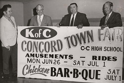 Four members of the Knights of Columbus, Concord Council, holding a sign for the Concord Town Fair, [dated 1971 but likely 1972].